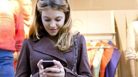 Close-up-portrait-of-a-young-stylish-teenager-woman-using-a-smartphone-device-while-visiting-the-city-leaning-on-a-fashion-store-shop-window-while-shopping-for-clothes-via-Shutterstock-615x345